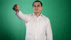 Retrato del hombre joven que lleva a cabo llave, aislado en verde almacen de video
