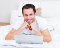 Retrato del hombre joven que miente en cama usando la computadora portátil Imágenes de archivo libres de regalías