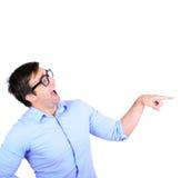 Retrato del hombre joven que ríe y que señala con el finger en alguno Foto de archivo