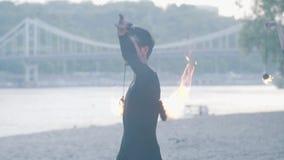 Retrato del hombre joven que realiza una demostración con la llama en el riverbank con un puente en el fondo Fireshow experto almacen de metraje de vídeo