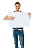 Retrato del hombre joven que señala en el letrero en blanco Fotos de archivo