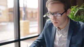 Retrato del hombre joven que se sienta en el café cerca de ventana con la opinión de la ciudad almacen de video