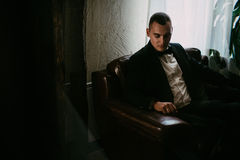 Retrato del hombre joven que se sienta en la silla y que mira abajo Imagen de archivo libre de regalías