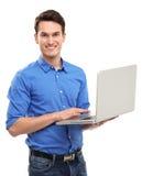 Retrato del hombre joven que sostiene la computadora portátil Foto de archivo