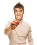 Retrato del hombre joven que sostiene la manzana roja Fotos de archivo