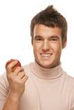Retrato del hombre joven que sostiene la manzana roja Foto de archivo libre de regalías