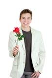 Retrato del hombre joven que sostiene la rosa sobre el fondo blanco Imágenes de archivo libres de regalías