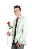 Retrato del hombre joven que sostiene la rosa sobre el fondo blanco Foto de archivo libre de regalías