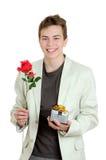 Retrato del hombre joven que sostiene la rosa y el regalo sobre el fondo blanco Fotos de archivo