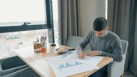 Retrato del hombre joven que trabaja en gráficos financieros en el café almacen de video