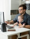 Retrato del hombre joven que trabaja en la oficina y que detiene a su hijo de 1 año del bebé Imágenes de archivo libres de regalías