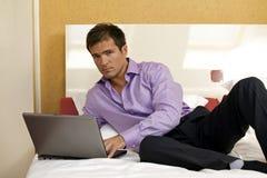 Retrato del hombre joven que usa el ordenador portátil en cama Fotos de archivo libres de regalías