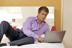 Retrato del hombre joven que usa el ordenador portátil en cama Fotografía de archivo libre de regalías
