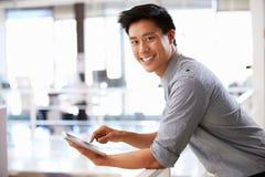 Retrato del hombre joven que usa la tableta en oficina Foto de archivo libre de regalías