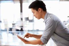 Retrato del hombre joven que usa la tableta en una oficina Foto de archivo