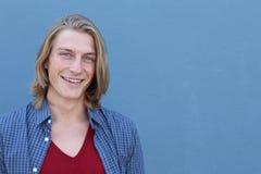 Retrato del hombre joven rubio casual que lleva la camisa de tela escocesa azul y la camiseta roja del cuello en v Imágenes de archivo libres de regalías