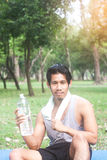 Retrato del hombre joven sano que sostiene la botella de agua en naturaleza Fotos de archivo