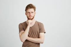 Retrato del hombre joven serio que piensa en vista de la mirada en lado sobre el fondo blanco Fotos de archivo