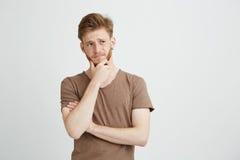 Retrato del hombre joven serio que piensa en vista de la mirada en lado sobre el fondo blanco Imagen de archivo libre de regalías