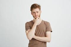 Retrato del hombre joven serio que piensa en vista de mirar la cámara sobre el fondo blanco Foto de archivo