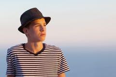Retrato del hombre joven serio y pensativo en fondo del cielo de la puesta del sol Imagenes de archivo