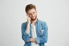 Retrato del hombre joven soñador que piensa mirando la cámara con la mano en mejilla sobre el fondo blanco Imagen de archivo libre de regalías