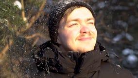 Retrato del hombre joven, sonriente con el bigote que disfruta de las nevadas en el bosque del invierno, bizqueando sus ojos del  almacen de metraje de vídeo
