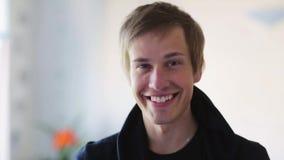 Retrato del hombre joven sonriente feliz dentro almacen de metraje de vídeo