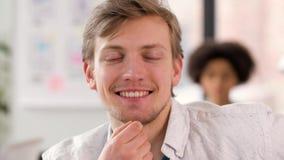Retrato del hombre joven sonriente feliz en la oficina almacen de video