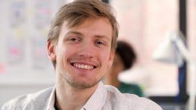 Retrato del hombre joven sonriente feliz en la oficina metrajes