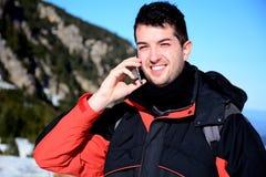 Retrato del hombre joven sonriente que habla en el teléfono en la montaña del invierno Fotografía de archivo