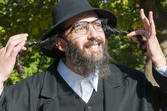 Retrato del hombre judío ortodoxo sonriente que sostiene Sidelocks largo, Peyot, Payot Foto de archivo libre de regalías