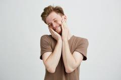 Retrato del hombre lindo hermoso joven que sonríe con las manos en mejillas y los ojos cerrados sobre el fondo blanco Fotos de archivo libres de regalías