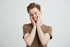 Retrato del hombre lindo hermoso joven que sonríe mirando la cámara con las manos en mejillas sobre el fondo blanco Foto de archivo