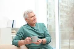 Retrato del hombre maduro con la taza de bebida imágenes de archivo libres de regalías