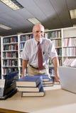 Retrato del hombre maduro en la biblioteca con los libros de textos Fotografía de archivo libre de regalías