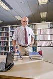 Retrato del hombre maduro en la biblioteca con los libros de textos Imagen de archivo