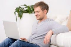 Retrato del hombre maduro feliz con el ordenador portátil en casa Imagenes de archivo