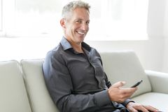 Retrato del hombre maduro que se relaja en casa en sofá y teléfono móvil Fotos de archivo libres de regalías