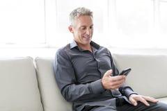 Retrato del hombre maduro que se relaja en casa en sofá y teléfono móvil Imágenes de archivo libres de regalías