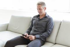 Retrato del hombre maduro que se relaja en casa en sofá y teléfono móvil Fotos de archivo