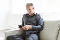 Retrato del hombre maduro que se relaja en casa en sofá y teléfono móvil Imagenes de archivo
