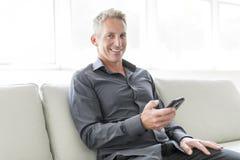 Retrato del hombre maduro que se relaja en casa en sofá y teléfono móvil Fotografía de archivo libre de regalías
