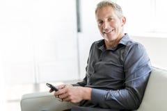 Retrato del hombre maduro que se relaja en casa en sofá y teléfono móvil Fotografía de archivo
