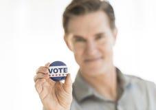 Retrato del hombre maduro que sostiene el botón del voto foto de archivo