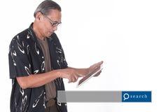 Retrato del hombre mayor asiático que usa el dispositivo elegante con engi de la búsqueda Imágenes de archivo libres de regalías
