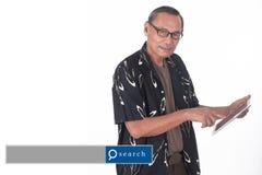 Retrato del hombre mayor asiático que usa el dispositivo elegante con engi de la búsqueda Imagenes de archivo