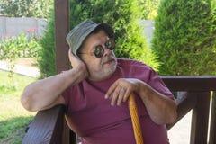 Retrato del hombre mayor barbudo en las gafas de sol que descansan mientras que se sienta en el mirador Imágenes de archivo libres de regalías