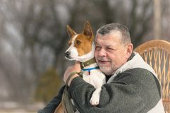 Retrato del hombre mayor caucásico con su perro lindo del basenji fotografía de archivo libre de regalías