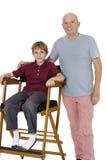 Retrato del hombre mayor con el muchacho pre-adolescente que se sienta en la silla del director sobre el fondo blanco Fotos de archivo libres de regalías